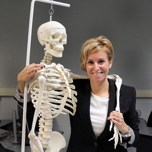 Woman smiling holding a model of a skeleton