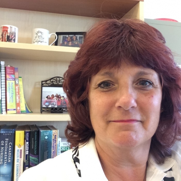 Woman in a lab coat smiling sitting a desk in front of a bookshelf